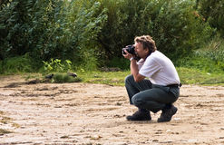 Photographer at work. Man with camera outdoors (on the river beach Stock Image