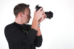 Photographer at work. A photographer shoots with his digital SLR camera stock image