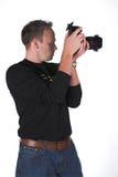 Photographer at work. A photographer shoots with his digital SLR camera stock photos