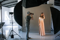 Photographer work in professional studio. Man taking shot of female model. Photo school, lookbook, fashion backstage concept Royalty Free Stock Photos