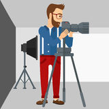 Photographer working with camera on a tripod. A photographer working with camera on the background of photo studio with lighting equipment vector flat design Stock Photo