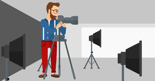 Photographer working with camera on a tripod. A photographer working with camera on the background of photo studio with lighting equipment vector flat design Royalty Free Stock Images
