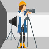 Photographer working with camera on a tripod. A photographer working with camera on the background of photo studio with lighting equipment vector flat design Stock Images