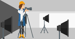 Photographer working with camera on a tripod. A photographer working with camera on the background of photo studio with lighting equipment vector flat design Royalty Free Stock Image