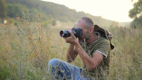 Photographer working outdoors. Photographer doing his job in the evening sun. Male photography shooting in a beautiful outdoor setting stock video footage