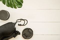Photographer working place with lens cover, black lens, case and tropical leaf flat lay top view. Photographer working place with lens cover, black lens, case Stock Images