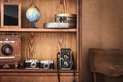 Photographer& x27; s-skåp Tappning franka kameror på träbakgrund Arkivfoto
