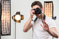 Photographer. Young smiling photographer with camera in professionally equipped studio Royalty Free Stock Image