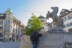 Photographer at Zurich streets. Taking a picture of the horse monument at the city streets. Zurich, Switzerland Royalty Free Stock Photography