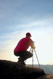 Photographerin red jacket and red baseball cap  stay with camera on  tripod on cliff and thinking. Dreamy landscape. Royalty Free Stock Photo