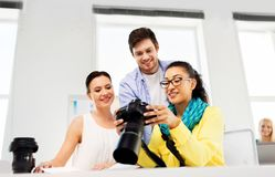Photographers with camera at photo studio. Photography and creative people concept - photographers with camera at photo studio stock images