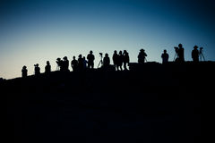 Photographers at Dawn. Silhouette of unidentified photographers awaiting sunrise on mountain ridge at Death Valley National Park royalty free stock images