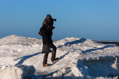 PHOTOGRAPHERS ON THE ICE. Two photographers photographing the frozen sea in winter stock image