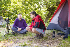 Photographers in Nature. Two photographers in nature near tent in summer day royalty free stock photos