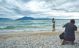 Photographers shooting on the sea beach at cloudy day Royalty Free Stock Image