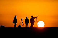 Photographers silhouetted against the setting sun. Three male photographers with their tripods set up silhouetted against the setting sun royalty free stock images