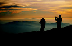 Photographers at sunset. Two photographers capture the sunset over the mountain range Royalty Free Stock Images