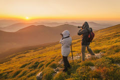 Photographers takes a sunset in the mountains. Nature photographers with digital camera and tripod on top of the mountain at sunset stock photos