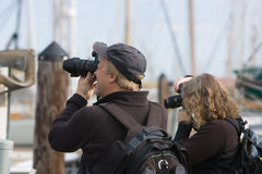 Photographers at work. Man and woman photographers using cameras to take different angles of outdoor scene Royalty Free Stock Photography