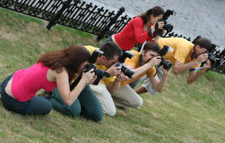 Photographers at work. Group of photographers on a grass aiming on target Royalty Free Stock Photo