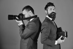 Photographers working. Men with beards hold photo cameras on blue background. Business or promotion concept. Reporters in classic suits work on event stock image