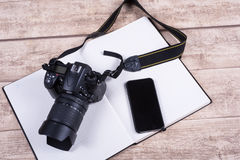 Photographers workplace with book, phone and camera on wooden ta Royalty Free Stock Image