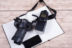 Photographers workplace with book, phone and camera on wooden ta Stock Photos