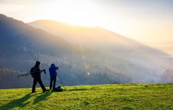 Photographers on workshop at sunrise. Capturing gorgeous scenery of mountainous area from the top of grassy hill. beautiful landscape with sun rising behind Stock Photo