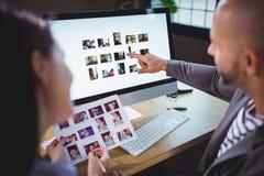 Photographes éditeur discutant au-dessus de l'ordinateur dans le bureau créatif images stock