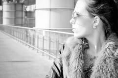 Photographie blanche noire de belle jeune dame sur le fond en verre de bâtiment de ville Photos stock