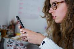 Photographie d'une fille regardant le mobile devant son ordinateur un bureau complètement des choses photographie stock