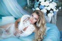 Photographie de boudoir Blonde de femme avec de longs cheveux dans la lingerie sur le lit entouré par des tulipes de fleurs Portr photos stock