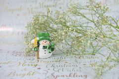 Photographie de Noël des fleurs vertes blanches avec le scintillement et du bonhomme de neige heureux mignon sur le fond de papie Image libre de droits