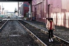 Photographie de rue de femme marchant sur des voies de train dans le secteur industriel Portland l'Orégon en décembre 2017 Images libres de droits