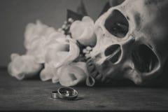 Photographie noire et blanche avec les anneaux, le crâne humain et les roses dessus Photos stock