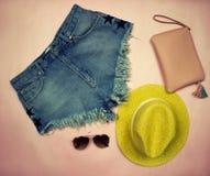 Photographie soumise Ensemble d'été de vêtements sur des shorts se composants d'un denim de fond rose, chapeau jaune, verres et Images stock