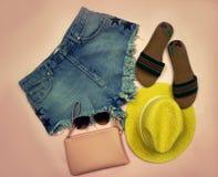 Photographie soumise Ensemble d'été de vêtements sur des shorts se composants d'un denim de fond rose, chapeau jaune, verres et Photos libres de droits
