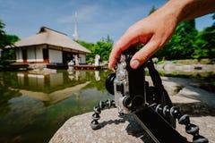Photographiez la main masculine manipulant un vieil appareil-photo de vintage sur le trépied devant l'étang d'eau avec la maison  images stock