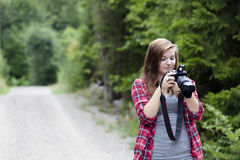 Photographing. Teenage girl holding a camera shooting a picture outdoors. She is looking at the back of the camera Royalty Free Stock Image