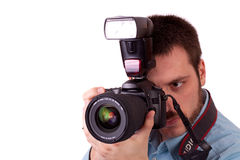 Photographing. Young man holding SLR camera in his hand and smiling Stock Photography