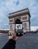 Photographing Arc de Triomphe with phone Stock Photography