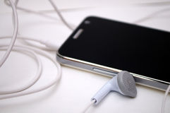 Photographing black phone with white headphones on a white background Royalty Free Stock Photo