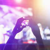Photographing with cell phone at the concert Royalty Free Stock Photos