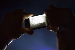 Photographing with cell phone at the concert Royalty Free Stock Photography