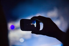Photographing with cell phone at the concert Royalty Free Stock Image
