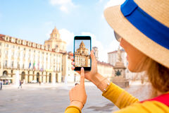 Photographing church in Turin city. Woman photographing with smartphone saint Lawrence church on the central square in Turin in Piedmont region in Italy stock photography