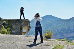 Photographing on the cliff. Two tourists are standing on the mountain edge and photographing Royalty Free Stock Photo