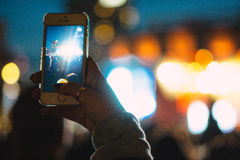 Photographing a concert. Person holds mobile phone up to photograph a music concert in Tivoli Park, Copenhagen Stock Images