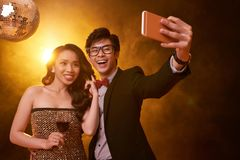 Photographing couple. Joyful Vietnamese couple photographing at night club Royalty Free Stock Photography