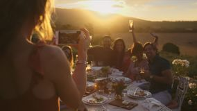 Photographing dinner party. Group of young friends sitting around table and posing while a woman taking their picture with her mobile phone. Female taking stock footage